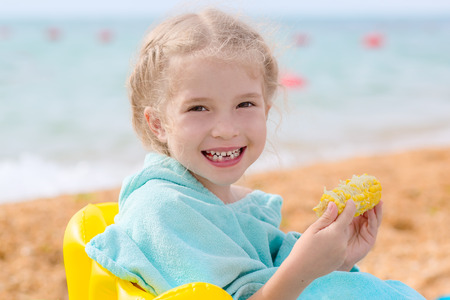 Portrait of Smiling Little Girl eating corn on the beach. Stock Photo