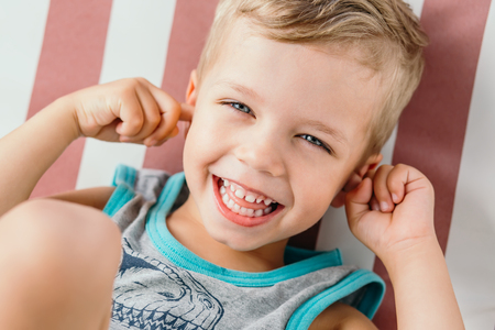happy little boy covering his ears and laughing Stock Photo