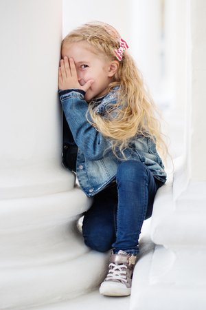 Happy little girl playing peekaboo on a white background