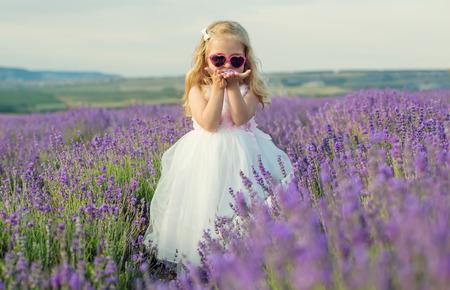 Girl in white dress walking in lavender field Stock Photo