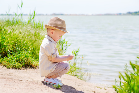 Little boy is sitting on the lake and playing with spikelet photo