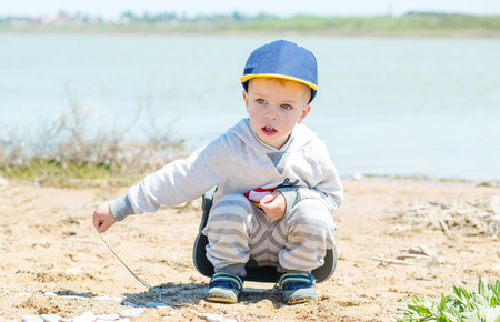 Little boy is sitting on the shore of the lake and playing with stones and sand photo