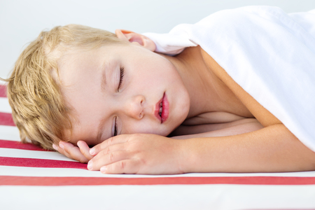 close-up portrait of a beautiful sleeping kid on striped photo