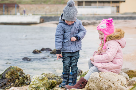 two small kids playing together outdoors. siblings exploring seaside. two preschoolers actively playing on stony beach, countryside life with children.