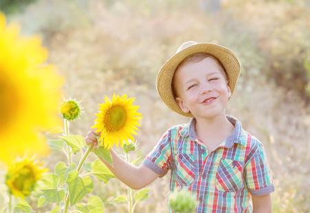 Happy little boy on the field of sunflowers in summer