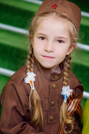 Adorable little girl in military uniform on 9 of may, the day of victory. Great Patriotic War. World War II.  Stock Photo
