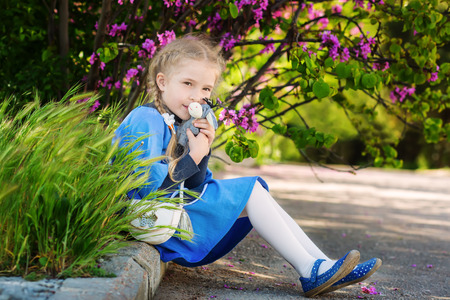 Cute little girl with a favorite toy donkey sitting on the background of a flowering bush Stock Photo