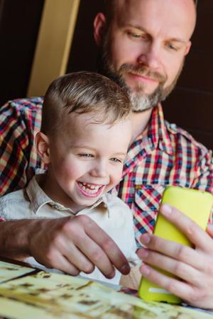 Papa avec son fils jouant avec un smartphone