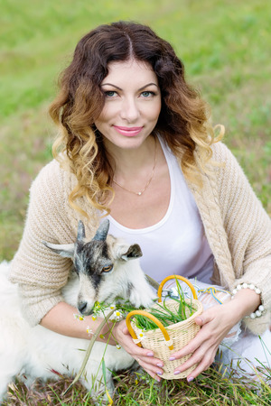 Beautiful woman is feeding a young goat grass in the spring Stockfoto