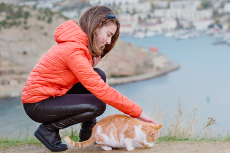 A teenage girl on a walk by the sea and strokes a cat