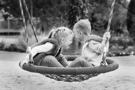 two happy little children having fun on a swing on autumn day (black and white) 免版税图像