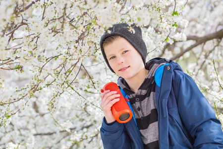 happy boy teenager with portable wireless speaker listening to music on the background of a blossoming tree Stock Photo