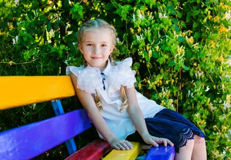 Charmant klein schoolmeisje zittend op een bankje op het schoolplein Stockfoto