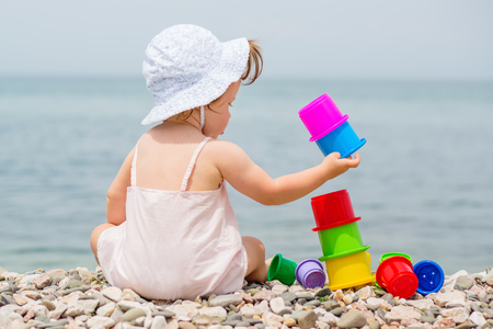 Cute toddler girl playing with colorful toys on the beach