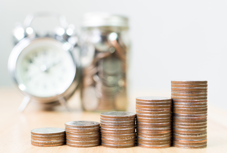 Coin stack step growing up to success financial business with clock and jar, Save money and investment concept