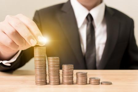 De zakenmanhand die muntstukstapel opvoeren verhoogt sparen geld, Financiën en investeringsconcept Stockfoto