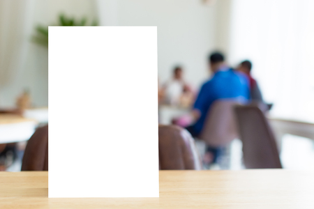 Mock up blank template menu frame on wood table in restaurant with blurred background, Clipping path included