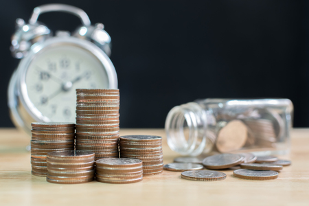 Coin stack with blurred clock and jar background, Finance and investment save money concept
