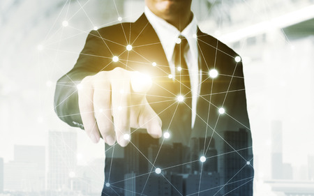 Network and Connection technology concept, Double exposure of businessman hand touching world map point with building in the city Stockfoto