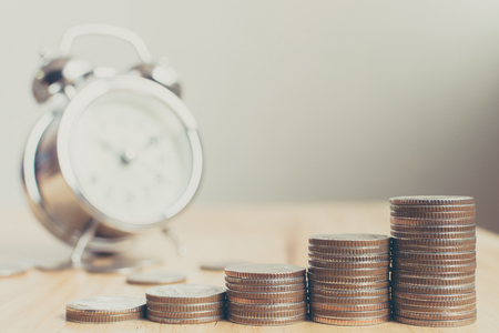 Pile de pièces placées sur des escaliers sur une planche de bois avec horloge, finances et investissement ont augmenté en valeur au fil du temps