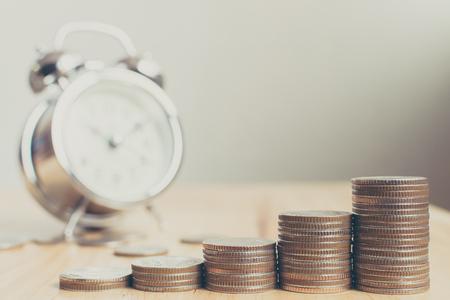Stos monet umieszczonych na schodach na drewnianej desce z zegarem, finanse i inwestycje zyskały na wartości w czasie