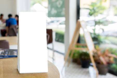 Mock up blank template menu frame on wood table in restaurant with blurred background