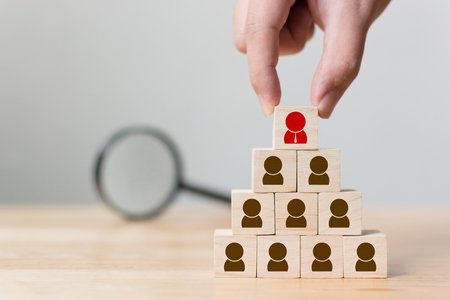 Human resource management and recruitment business concept, Hand putting wood cube block on top pyramid and magnifying glass, Copy space Stockfoto