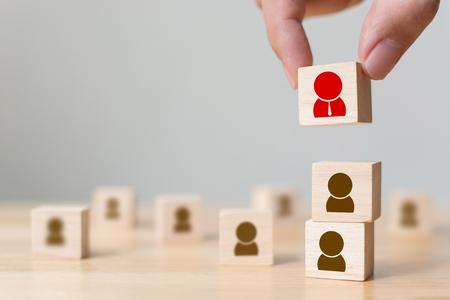 Personalmanagement und Einstellungsgeschäft bauen Teamkonzept auf, übergeben das Setzen des hölzernen Würfelblocks auf die Oberseite, kopieren Raum Standard-Bild