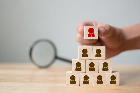 Concepto de negocio de gestión de recursos humanos y reclutamiento, mano poniendo bloque de cubo de madera en la pirámide superior y lupa, espacio de copia