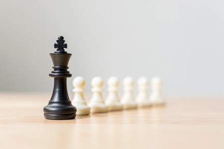 Black chess figure leading white chess on wood table, Success of business leader concept