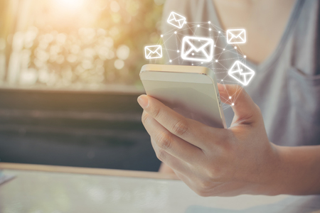 Mano de mujer asiática con teléfono móvil con aplicación de correo electrónico, boletín de correo electrónico de concepto y protección antivirus contra correo no deseado