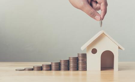 Immobilieninvestitions- und Haushypothekenfinanzkonzept, Hand, die Geldmünzenstapel mit Holzhaus steckt