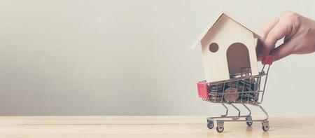 Concepto financiero de la inversión inmobiliaria y de la hipoteca de la casa, moneda de la casa y del dinero en carro de compras