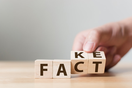 Fact or Fake concept, Hand flip wood cube change the word, April fools day Stockfoto