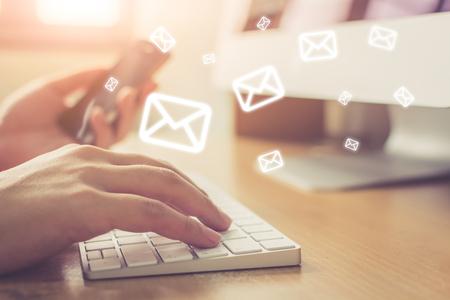 Concetto di email marketing e newsletter, mano dell'uomo che invia messaggio e telefono cellulare con icona di posta elettronica