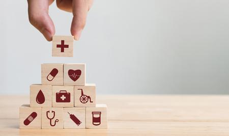 Ręcznie układanie bloków drewnianych z ikoną opieki zdrowotnej, ubezpieczenie dla swojej koncepcji zdrowia