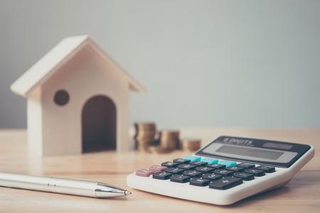 Calcolatrice con casa in legno e pila di monete e penna sulla tavola di legno. Investimento immobiliare e concetto finanziario mutuo casa Archivio Fotografico