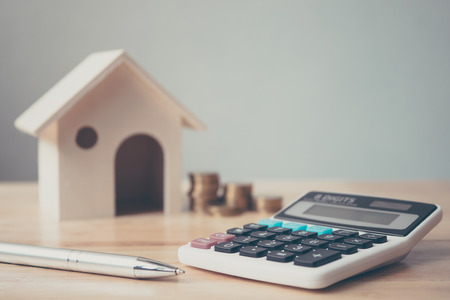 Calculator with wooden house and coins stack and pen on wood table. Property investment and house mortgage financial concept 免版税图像 - 105210717