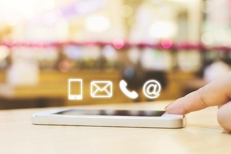 Main de femme poussant le bouton smartphone, connexion d'affaires nous contacter concept, icône de téléphone mobile, adresse e-mail, téléphone et e-mail Banque d'images