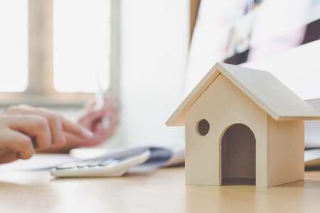 Wooden home model and key house on wood table with hand signing the document contract loan or mortgage property investment Stock Photo