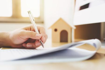 Bliska ręka mężczyzny podpisywania dokumentu pożyczki podpisu na własność domu. Kredyty hipoteczne i inwestycje w nieruchomości