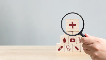 Hand holding magnifying glass to wood block stacking with icon healthcare medical, Insurance for your health concept Foto de archivo