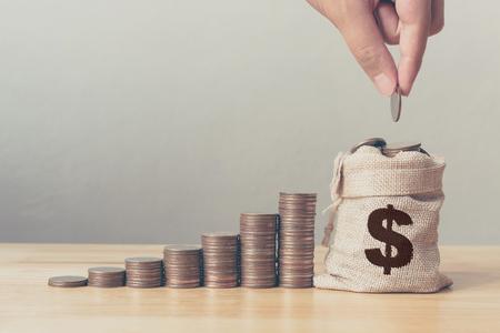 Hand des Mannes oder der Frau, die Münzen in Geldsack mit Münzstapelschritt setzt, wächst wachstumssparendes Geld, Konzeptfinanzierungsgeschäftsinvestition