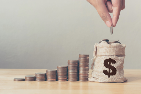 Hand of male or female putting coins in money bag with coin stack step growing growth saving money, Concept finance business investment Stock Photo
