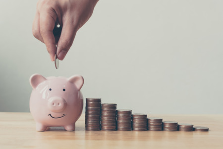 Hand of male or female putting coins in piggy bank with money stack step growing growth saving money. Concept finance business investment 写真素材