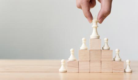 Geschäftsführungskonzept mit Schach auf oberster Holzblockleitertreppe. Teamleitende Karriere für Teamarbeit
