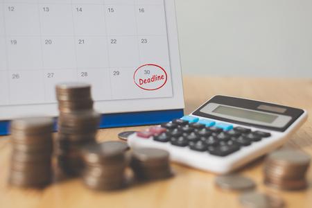 Temporada de pago de impuestos y concepto de fecha límite de cobro de deuda financiera. Pila de monedas de dinero, calendario y calculadora