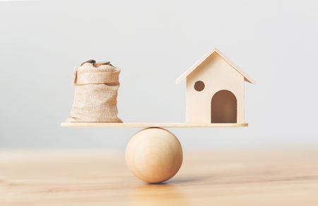 Wooden home and coins money in bag on wood scales. Property investment and house mortgage financial real estate concept Foto de archivo