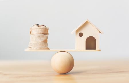 Houten huis en muntstukkengeld in zak op houten schalen. Investeringen in onroerend goed en huis hypotheek financieel onroerend goed concept