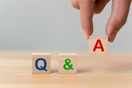 Questions and answers concept. Hand putting wood block cube with alphabet Q&A on wooden table
